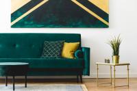 Zelená pohovka a zlatý odkladací stolík v glamour obývačke