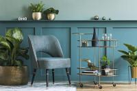 Sivá čalúnená stolička a servírovací stolík na kolieskach