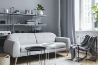 Svetlá pohovka a okrúhle kovové stolíky v bielej obývačke