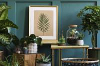 Zlatý stolík s rastlinnými dekoráciami pri modrej stene