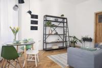Okrúhly stôl a kovový regál v škandinávskej obývačke