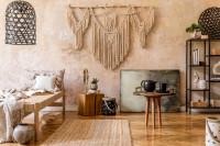 Okrúhly stolík a prírodné boho doplnky v béžovej obývačke