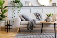 Svetlá pohovka so sivou dekou a drevený stolík
