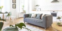 Sivá pohovka vo svetlej obývačke s kuchyňou