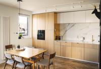 Moderná svetlá kuchynská linka a drevený jedálenský stôl s čalúnenými stoličkami
