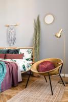 Manželská posteľ a okrúhle kreslo v bohémskej spálni