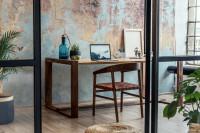 Drevený písací stôl a stolička v industriálnej pracovni