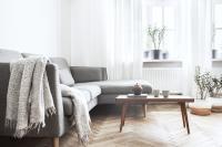 Sivá rohová pohovka s dekou a nízky konferenčný stolík