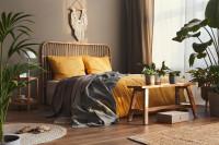 Posteľ so žltými obliečkami a drevená lavica v boho spálni