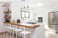 Moderná kuchynská linka s dreveným pultom a bielymi barovými stoličkami