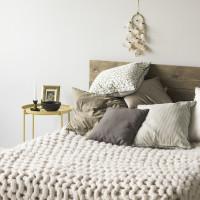 Drevená manželská posteľ a dekoračné vankúše v škandinávskej spálni