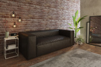 Tmavá kožená pohovka v obývačke s odkrytou tehlovou stenou