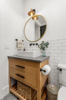 Okrúhle zrkadlo v bielej kúpeľni s dreveným nábytkom