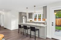 Čierne barové stoličky vo svetlej klasickej kuchyni