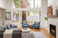 Rohová sedačka a modré kreslá v obývačke s vysokým stropom