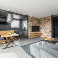 Drevený nábytok a tehlová stena v industriálnej obývačke s kuchyňou