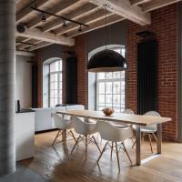 Dlhý jedálenský stôl a biele plastové stoličky v industriálnej jedálni