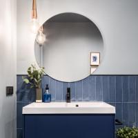 Okrúhle zrkadlo a biele umývadlo v elegantnej modrej kúpeľni