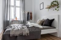 Drevená manželská posteľ a stojanový vešiak v malej spálni