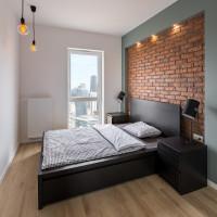 Čierna manželská posteľ v spálni s výraznou tehlovou stenou