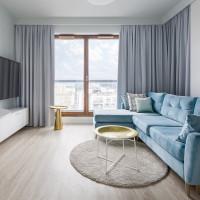 Modrá rohová pohovka a okrúhle konferenčné stolíky v modernej obývačke