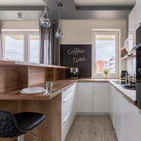 Biela kuchynská linka s pracovnou doskou zo svetlého dreva