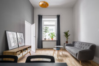 Elegantná sivá pohovka a sada drevených konferenčných stolíkov