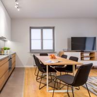 Dlhý jedálenský stôl a čierne stoličky v priestrannej modernej kuchyni