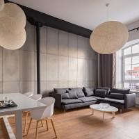 Sivá rohová sedačka a okrúhly konferenčný stolík v industriálnej obývačke