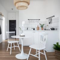 Biela kuchynská linka a okrúhly jedálenský stôl v malej kuchyni