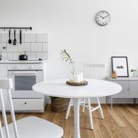 Biela kuchynka s okrúhlym jedálenským stolom