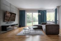 Sivá rohová sedačka a okrúhle konferenčné stolíky v priestrannej modernej obývačke
