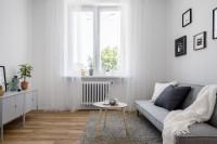 Svetlá pohovka a okrúhly konferenčný stolík v malej obývačke