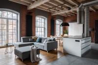 Svetlá rohová pohovka v priestrannej industriálnej obývačke s kuchyňou