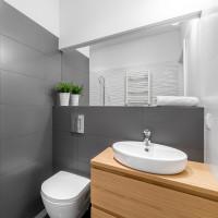 Drevená skrinka s umývadlom v modernej sivej kúpeľni