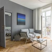 Sivá pohovka a konferenčný stolík s mramorovou doskou