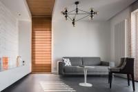 Sivá látková pohovka vo svetlej minimalistickej obývačke