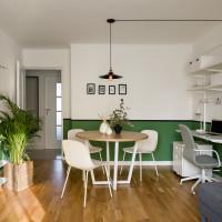 Okrúhly jedálenský stôl a biele stoličky v malom apartmáne