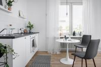 Okrúhly stôl a jedálenské stoličky v jednoduchej sivobielej kuchyni