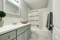 Kúpeľňová skrinka a nástenné zrkadlo v bielo-sivých tónoch