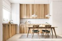 Drevený jedálenský stôl a stoličky vo svetlej škandinávskej kuchyni