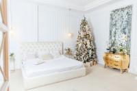 Biela manželská posteľ a zlatá baroková komoda v priestrannej spálni s vianočným stromčekom