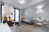 Sivá pohovka a jedálenský stôl s drevenými stoličkami