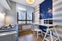 Biely pracovný stôl a stolička v študentskej izbe s modrou stenou