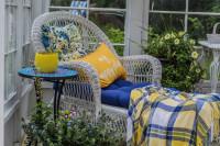 Biele ratanové kreslo a okrúhly odkladací stolík v zimnej záhrade