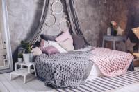 Veľká posteľ s pletenými dekami v sivých a ružových tónoch