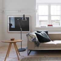 Béžová pohovka a drevený stolík v škandinávskej obývačke