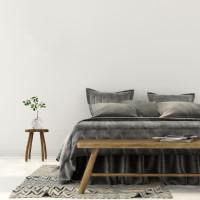 Spálňa v sivo-bielej kombinácii s drevenými doplnkami