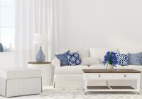 Pohovka a modré dekoračné vankúše v bielej obývačke