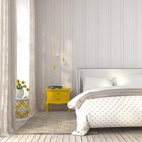 Manželská posteľ a žltý nočný stolík vo svetlej spálni